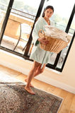 Woman carrying a full laundry basket Royalty Free Stock Photo