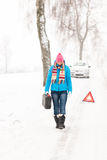 Woman carrying gas can snow car trouble. Winter breakdown walking stock image