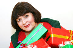 Woman carrying gifts. Smiling woman, holding gifts stock images