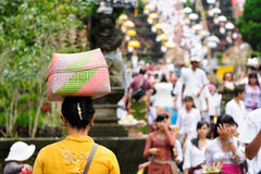 The woman is carrying gifts for Hindu gods on the head in the woven baske Royalty Free Stock Photo