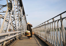 A woman carrying goods on the bridge in Hue, Vietnam Royalty Free Stock Images