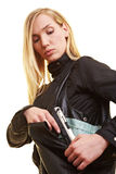 Woman carrying gun in handbag Stock Image