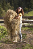 Woman carrying hay. Beautiful mid adult woman carrying hay at organic farm in the mountains Royalty Free Stock Image