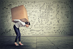 Woman carrying heavy box walking along gray wall. Young woman carrying heavy box walking along gray wall covered with writing of math science life ideas formulas Royalty Free Stock Photo