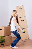 Woman Carrying Heavy Cardboard Boxes In House. Full length side view of young woman carrying heavy cardboard boxes in house Royalty Free Stock Photography