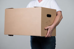 A woman is carrying a heavy cardboard on a grey background. A woman is carrying a heavy cardboard  on a grey background Stock Photos