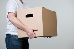 Woman is carrying a heavy cardboard with two hands,  on. A woman is carrying a big cardboard in his hands  on a grey background Stock Images
