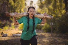 Woman carrying heavy wooden log during obstacle course royalty free stock photo