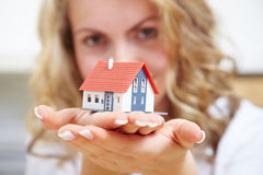 Woman carrying house on her hands royalty free stock photography