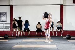 Woman Carrying Medicine Ball While Friends Exercising Stock Photos