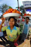Woman carrying oranges on her head for sell. Royalty Free Stock Photos