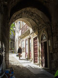Woman carrying packages walks up steep cobblestone street Lisbon Portugal Stock Images