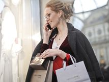 Woman Carrying Paper Bag and Holding Phone Stock Photography