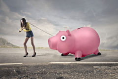 Woman carrying a piggy bank Royalty Free Stock Photos