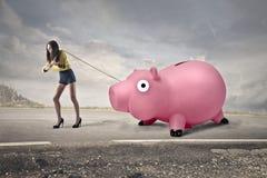 Woman carrying a piggy bank Royalty Free Stock Photos