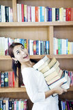 Woman carrying pile of books Stock Photography