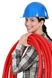 A woman carrying pipes. Royalty Free Stock Image