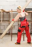 Woman carrying plank boards on construction site royalty free stock images