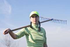Woman carrying rake Royalty Free Stock Image