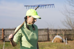 Woman carrying rake Stock Image