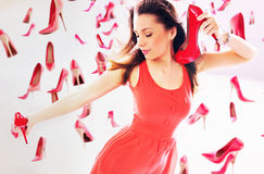 Woman carrying red high-heel shoes Royalty Free Stock Image