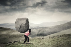 Woman carrying a rock on mountain Royalty Free Stock Image