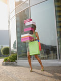 Woman carrying shoe boxes. Hispanic woman balancing stack of shoe boxes out of shopping center. Vertical shape, full length, copy space Stock Images