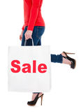 Woman Carrying Shopping Bag Advertising Sale. Close-up of Young Woman Carrying Shopping Bag Advertising Sale Isolated on White Royalty Free Stock Image
