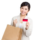 Woman carrying shopping bag and credit card. Isolated on white Stock Images