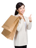Woman carrying shopping bag and thumb up. Isolated on white Royalty Free Stock Image
