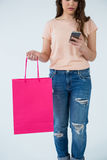 Woman carrying shopping bag and using mobile phone Royalty Free Stock Photo