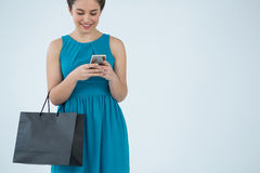 Woman carrying shopping bag and using mobile phone Stock Image