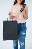 Woman carrying shopping bag and using mobile phone Royalty Free Stock Photos