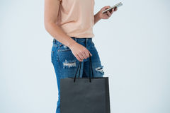 Woman carrying shopping bag and using mobile phone Stock Images