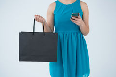 Woman carrying shopping bag and using mobile phone Stock Photo