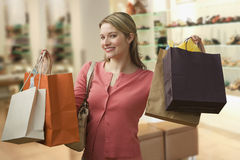 Woman Carrying Shopping Bags. Beautiful young woman shows an ecstatic expression while holding shopping bags in a store. Horizontal shot stock images
