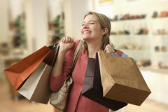 Woman Carrying Shopping Bags. Beautiful young woman shows an ecstatic expression while holding shopping bags in a store.  Horizontal shot Stock Image