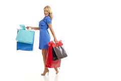 Woman carrying shopping bags. Woman in blue dress carrying shopping bags Stock Images