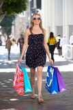 Woman Carrying Shopping Bags On City Street Stock Photography