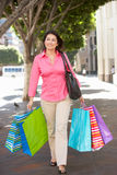 Woman Carrying Shopping Bags On City Street Stock Photo