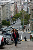 Woman Carrying Shopping Bags Climbs Steep Steps In Nob Hill. San Francisco, CA, USA - May 18, 2015:  A young woman carrying shopping bags climbs a very steep set Stock Photography