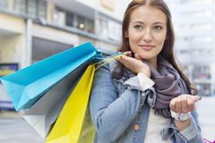 Woman carrying shopping bags while looking away Stock Photos