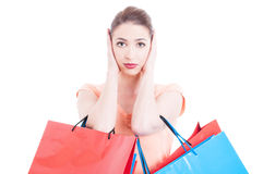 Woman carrying shopping bags making deaf gesture Royalty Free Stock Photography