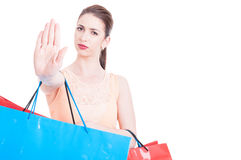 Woman carrying shopping bags making stop or refusal gesture Royalty Free Stock Images