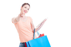 Woman carrying shopping bags pointing at camera and holding tabl Royalty Free Stock Photo