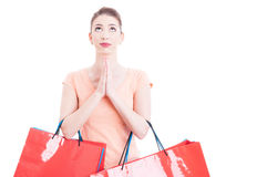 Woman carrying shopping bags praying and hoping for something Royalty Free Stock Images