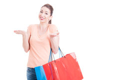Woman carrying shopping bags questioning and raising shoulders Stock Images