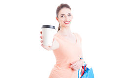 Woman carrying shopping bags showing or offering paper coffee mu Royalty Free Stock Photography