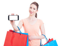 Woman carrying shopping bags smiling and showing blank mobile co Stock Image