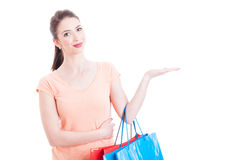 Woman carrying shopping bags smiling and showing blank space Royalty Free Stock Image